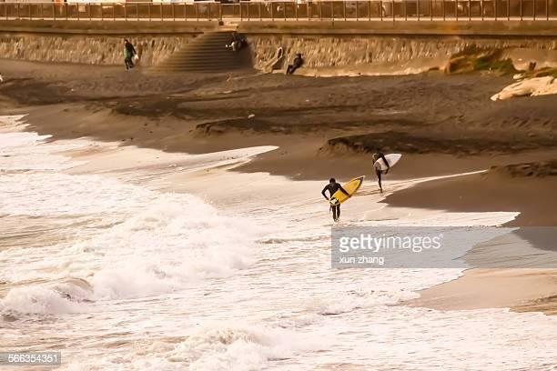 Some surfers are walking on the shoreline in Shonan beach Enoshima island Kanagawa Japan November 28 2010