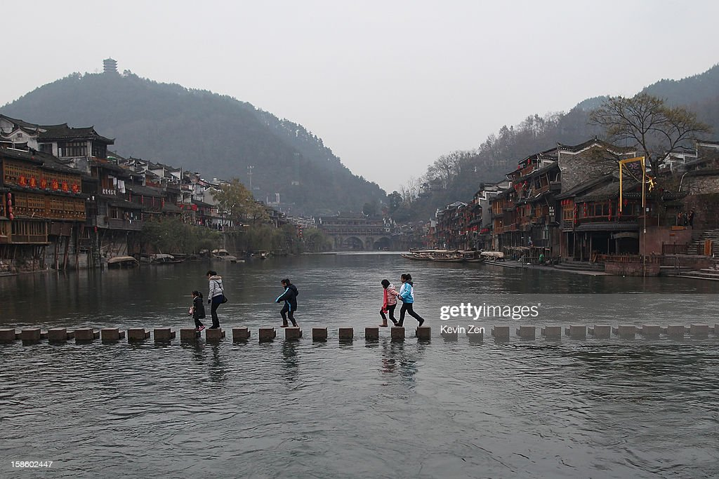 Some tourists go through a stone bridge on Tuojiang River on December 18, 2012 in Fenghuang, China. Fenghuang Town was built by Emperor Kangxi in 1704 and after 300 years, the city's ancient appearance has been well preserved. Hunan is located in southwest Hunan Provience of China with a population of 370,000 within a total area of 1700 square kilometers.