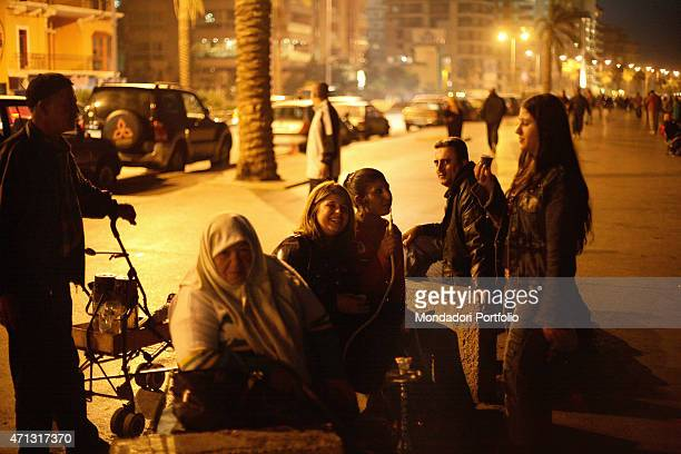 Some women smoking the hookah seated on a bench on the Corniche Beirut Lebanon January 2006