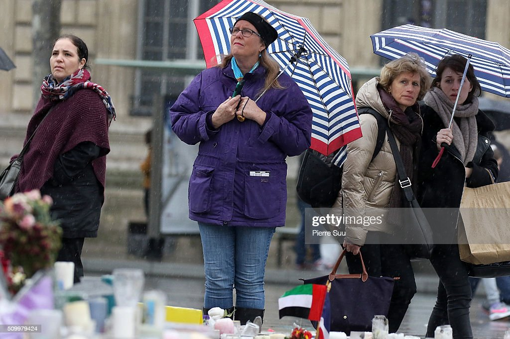 Some women stand in front of the monument at the Republique square on February 13, 2016 in Paris, France. People continue to leave tributes to victims three months after the Paris terrorist attacks.