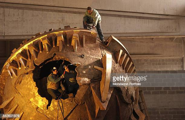 Some workers refining Italian sculptor Arnaldo Pomodoro's Grande Sfera being created for the Exhibition in the PalaisRoyal gardens in Paris Milan...