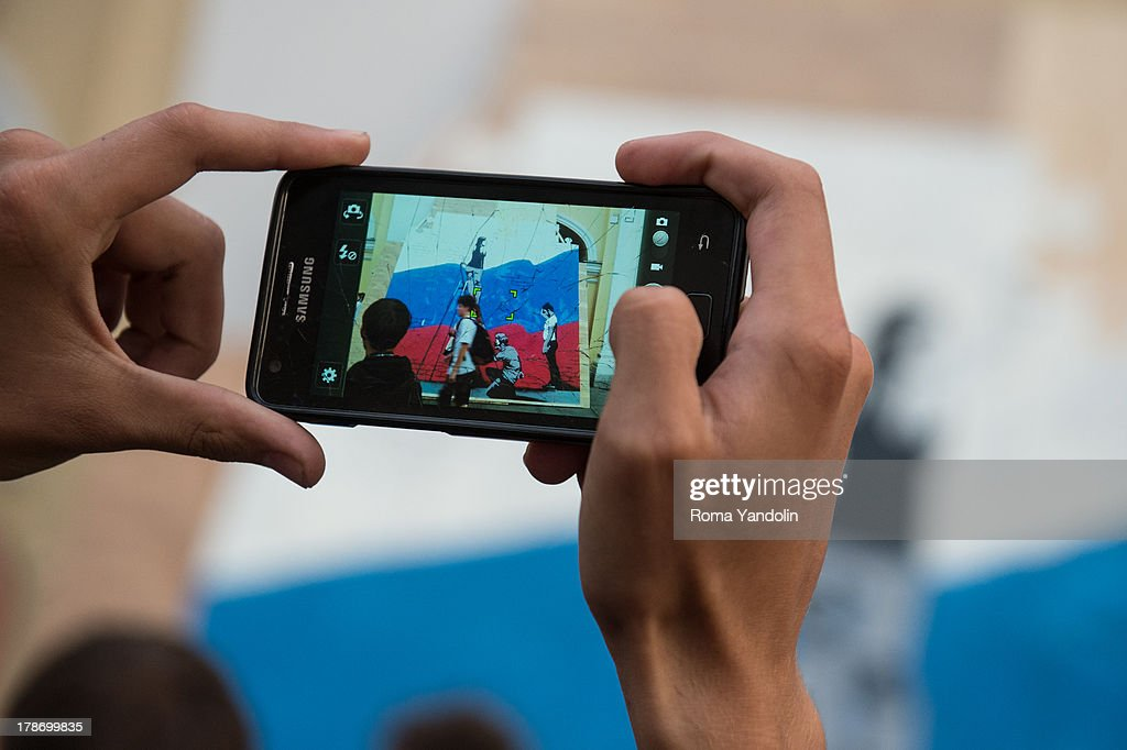 CONTENT] A somebody takes a photo with Samsung smartphone of a big graffiti with a flag of Russia that was painted on a puzzle during National Flag Day in St. Petersburg, Russia, August 22, 2013. The National Flag Day is an official holiday in Russia, established in 1994. It is celebrated on 22 August, the day of the victory over Putschists in 1991, but it is not a day-off.
