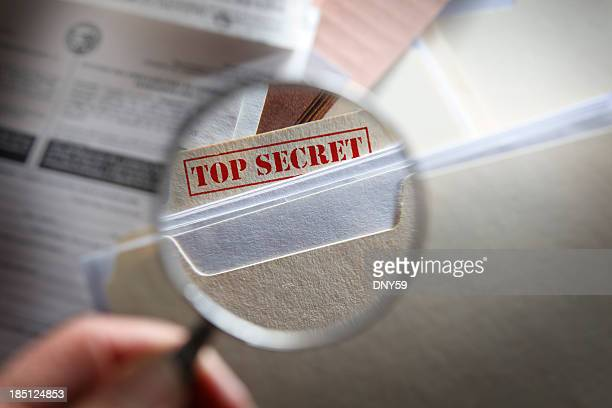 Someone looking at top secret files with magnifying glass