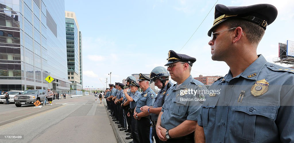 MIT, Somerville and Cambridge police line up across from the courthouse. At right is MIT's Deputy Chief Jay Perault. Media and supporters of victims of the Boston Marathon bombings gather outside the John Joseph Moakley United States Courthouse during the appearance of suspect Dzhokhar Tsarnaev, Wednesday, July 10, 2013.