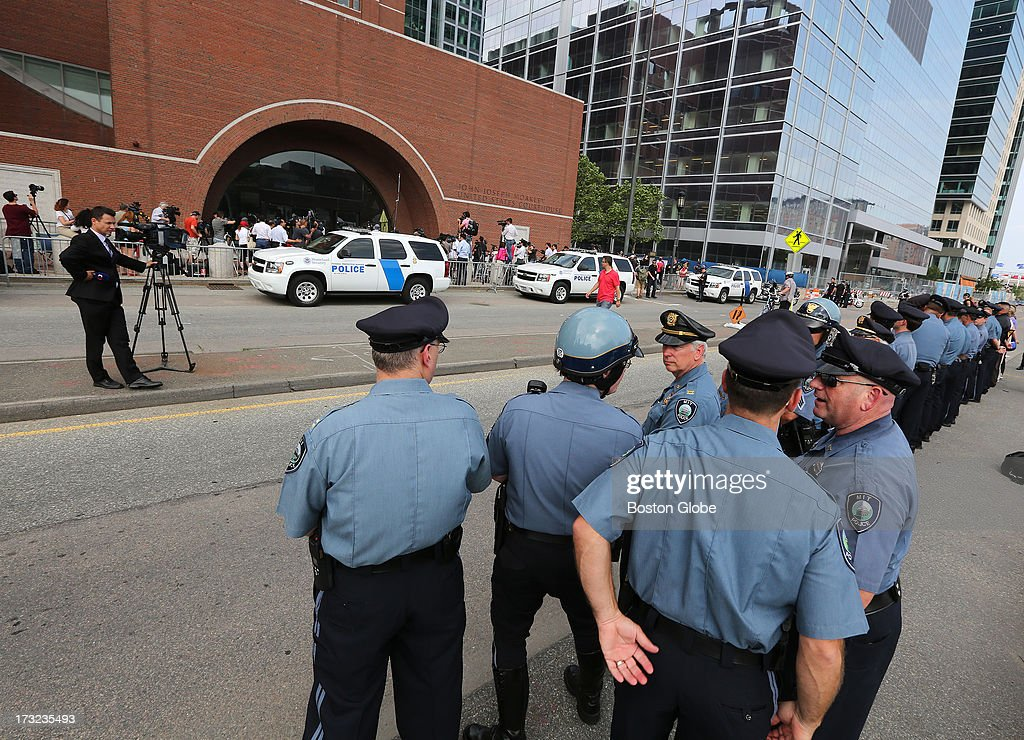 MIT, Somerville and Cambridge police line up across from the courthouse. Media and supporters of victims of the Boston Marathon bombings gather outside the John Joseph Moakley United States Courthouse during the appearance of suspect Dzhokhar Tsarnaev, Wednesday, July 10, 2013.