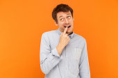 Something is stuck between teeth. Funny young adult business man touching finger teeth and looking up. Studio shot, orange background