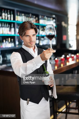 Sommelier examining glass of red wine in bar : Stock Photo