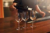 Sommelier pours pinot gris wine in glasses for degustation