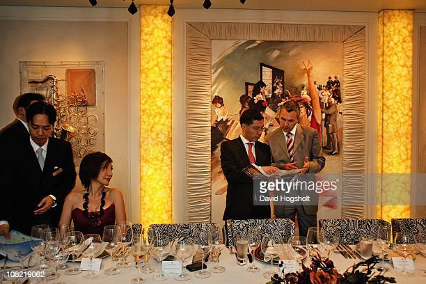 Sommelier JeanLuc Chapel talks to a guest about the wine list at a private dinner and wine tasting party August 4 2009 in Hong Kong Brand ambassador...