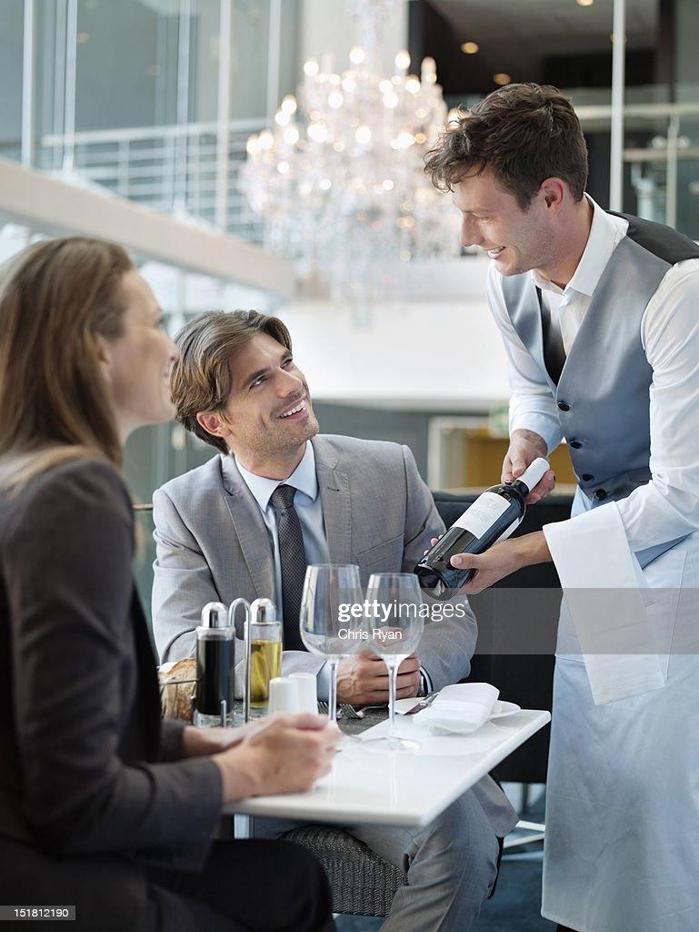 Sommelier presenting wine bottle to couple in restaurant : Stock Photo
