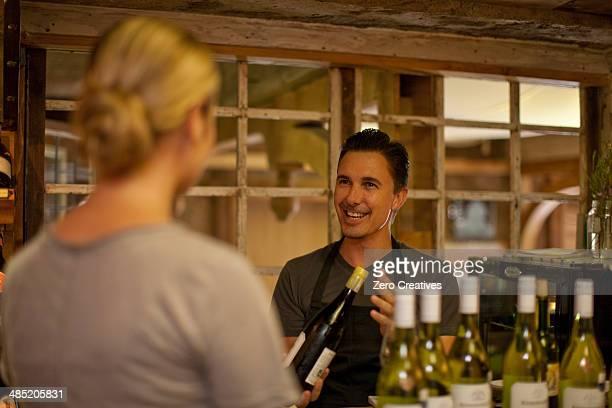 Sommelier selecting bottle of wine in wine shop