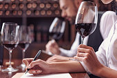 Two sommeliers, male and female tasting red wine and making notes at degustation card
