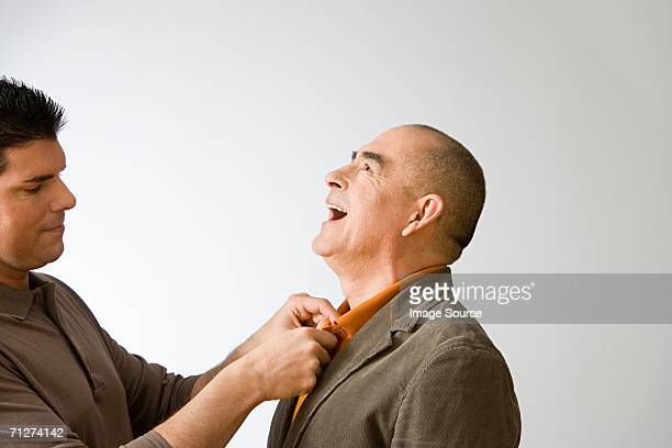 Son adjusting father's collar