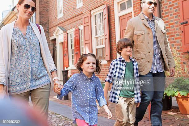Son (8-9) and daughter (6-7) walking with parents along town street, Philadelphia, Pennsylvania, USA