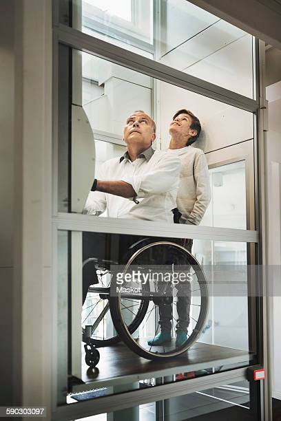 son and father in wheelchair lift at home