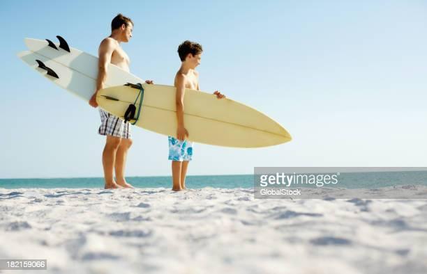 父と息子と、サーフボードの上に立つビーチ