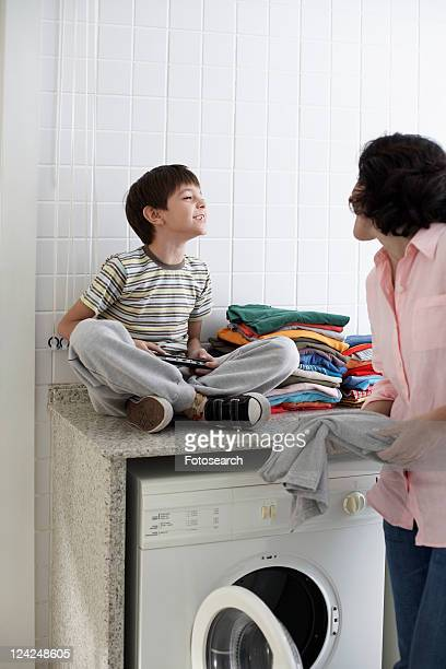 Son and mother grinning to each other in laundry room