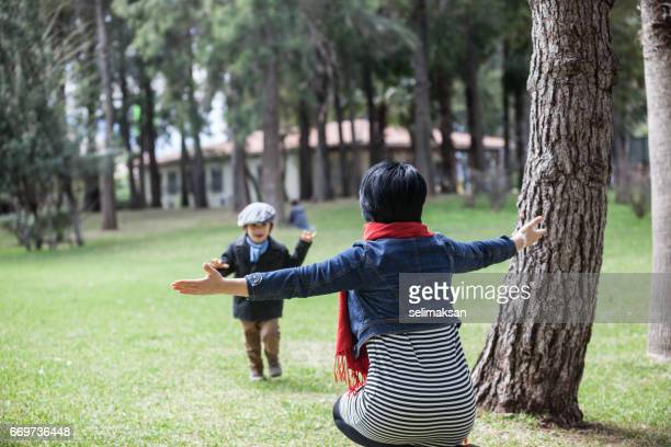 Son And Mother Playing In Green Public Park