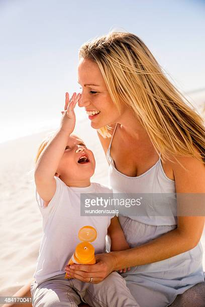 Son applying sunblock on mom's nose