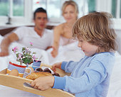 Son (4-6) bringing breakfast tray to parents sitting up in bed