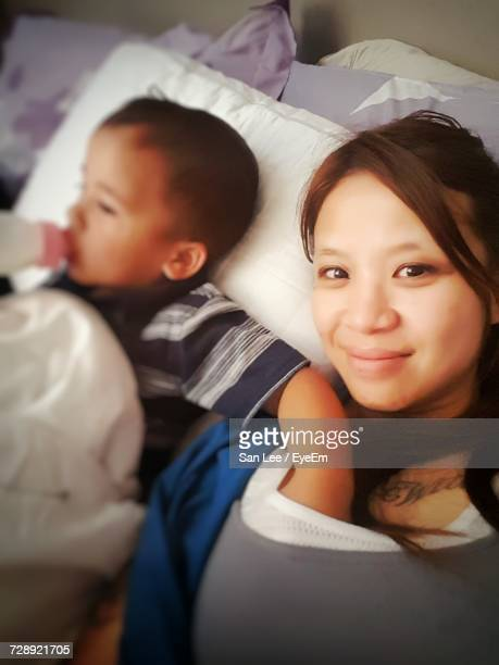 Son Drinking Milk While Touching Mother Breast Lying On Bed At Home