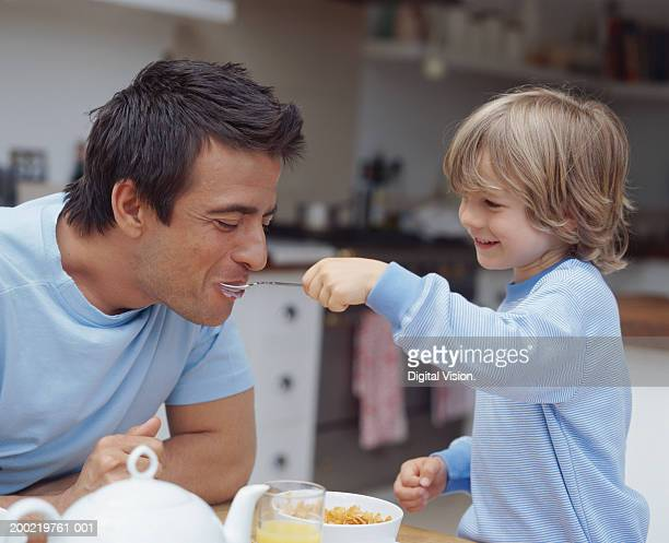 Son (4-6) feeding father cereal, smiling