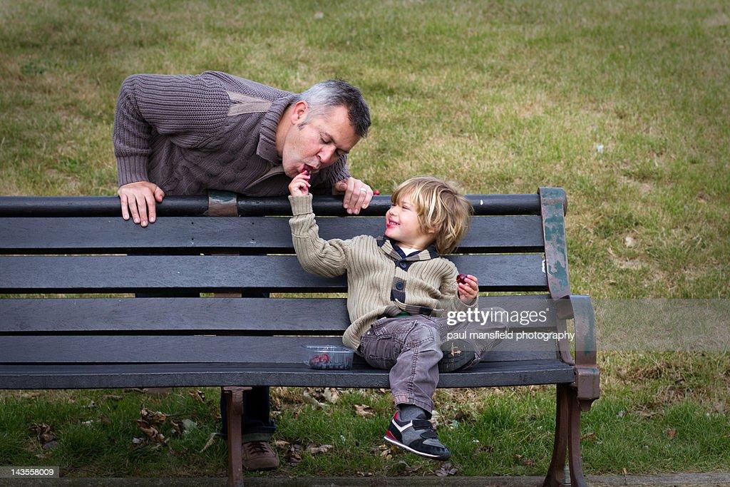 Son feeding father snack : Stock Photo