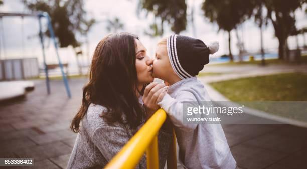Zoon een kus geven aan zijn moeder op de speelplaats