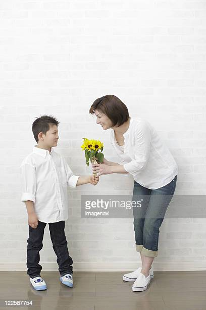 Son giving bouquet to mother