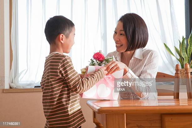 Son giving flower and gift to mother