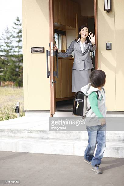 Son going out of front door and mother watching after