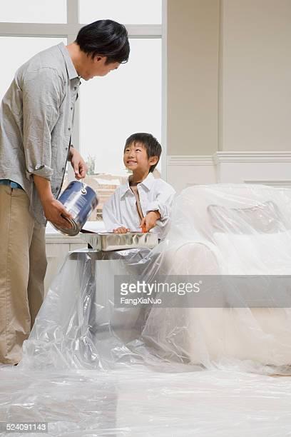 Sohn hilft seinem Vater Farbe ein Zimmer