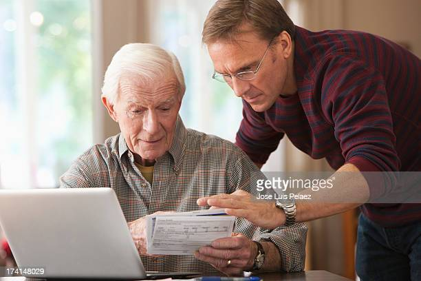 Son Helping his senior dad with his finances