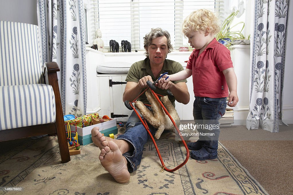 son helps dad to fix his toy : Stock Photo