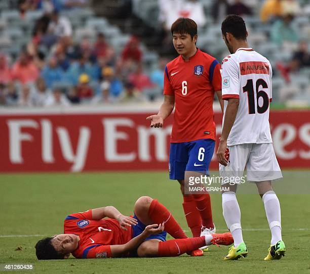 Son Heung Min of South Korea reacts on the ground watched by Park Joo Ho of South Korea and Ali Sulaiman Al Busaidi of Oman during the first round...