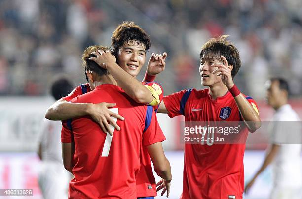 Son HeungMin of South Korea celebrates with Ki SungYueng after scoring a goal during the 2018 FIFA World Cup Qualifier Round 2 Group G match between...
