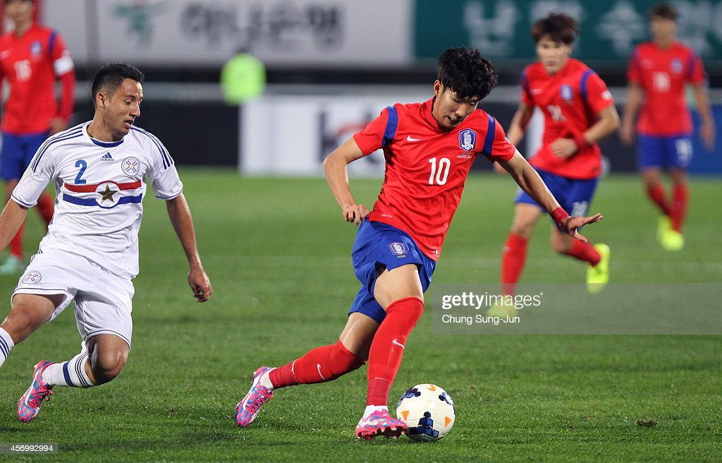 Son Heung-Min of South Korea competes for the ball with <a gi-track='captionPersonalityLinkClicked' href=/galleries/search?phrase=Ivan+Piris&family=editorial&specificpeople=5348316 ng-click='$event.stopPropagation()'>Ivan Piris</a> of Paraguay during the international friendly match between South Korea and Paraguay at Cheonan Sports Complex on October 10, 2014 in Cheonan, South Korea.