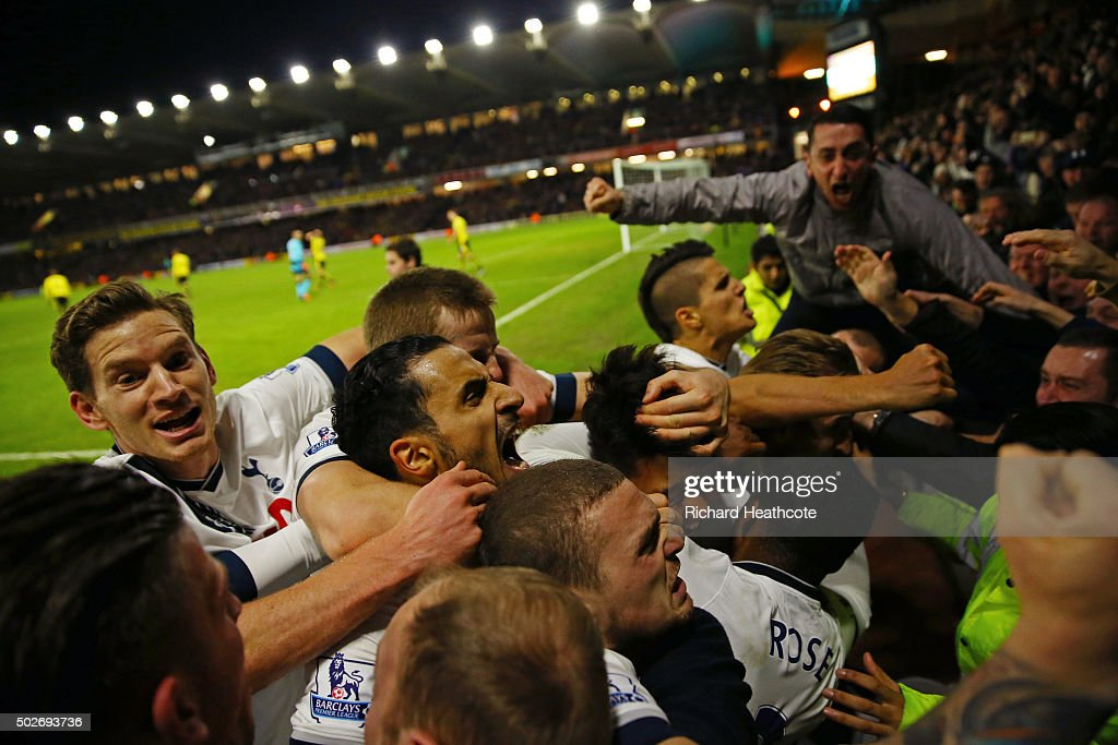 Son Heung-min (obscured) of Tottenham Hotspur celebrates scoring his team's second goal with his team mates and supporters during the Barclays Premier League match between Watford and Tottenham Hotspur at Vicarage Road on December 28, 2015 in Watford, England.