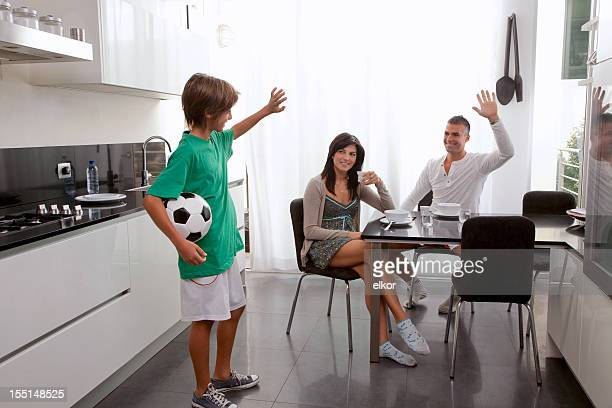 Son Holding Soccer Ball Waves Goodbye to Parents Having Breakfast