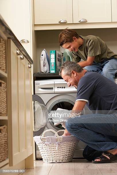 Son (9-11) in kitchen with father loading washing machine, smiling