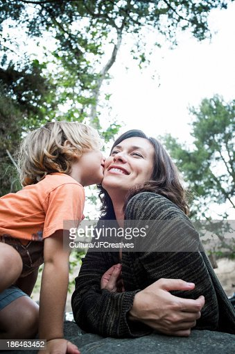 Son kissing mother in forest : Stock Photo
