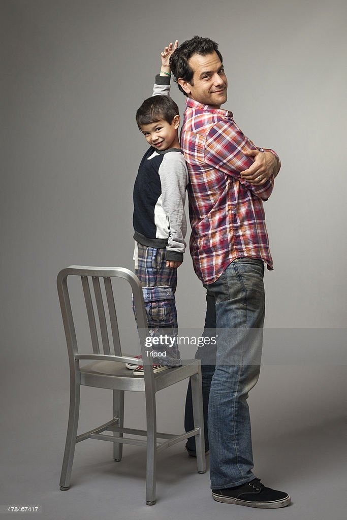 Son measuring height next to father : Stock Photo