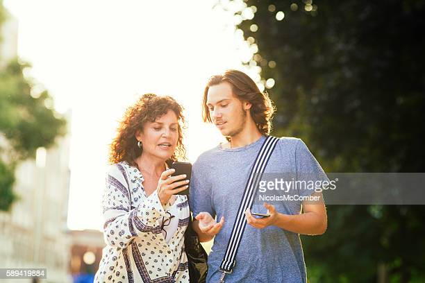 Son patiently explains smart phone to his mother