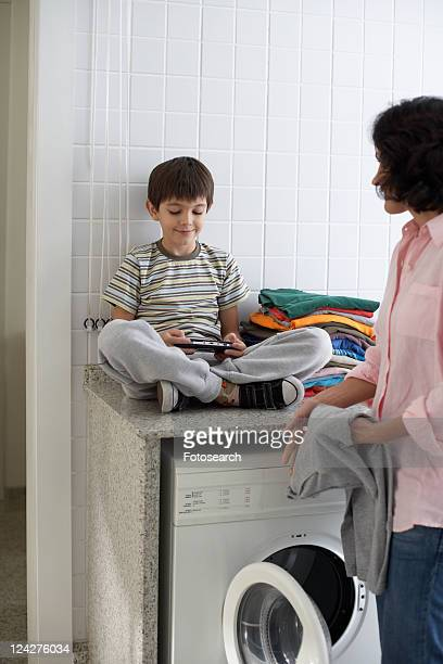 Son playing video game while mother loading washing machine
