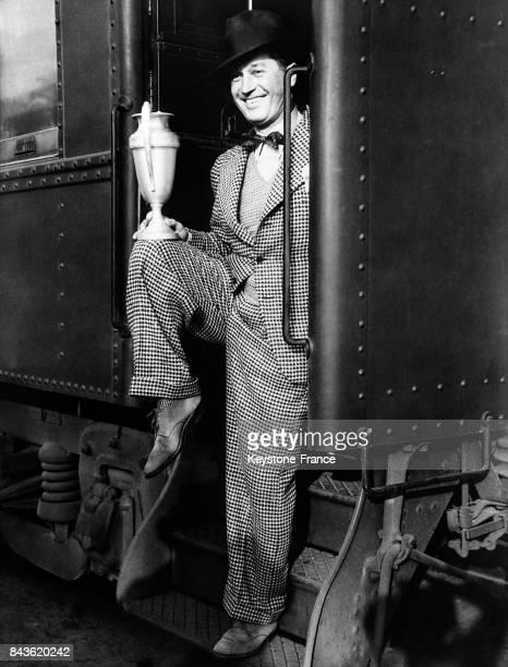 A son retour d'Hollywood Maurice Chevalier exhibe fièrement le trophée qu'il a gagné dans un concours de 'dégustateurs de vins' organisé pendant la...