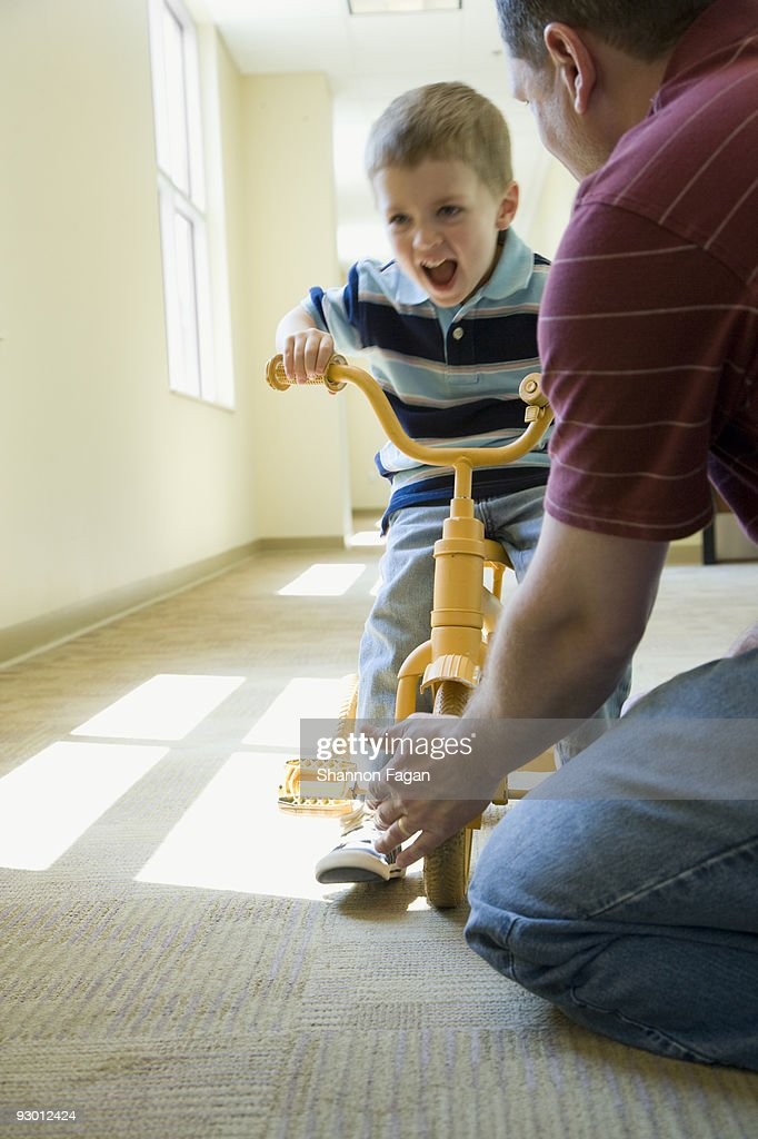 Son riding bicycle in Dad's office : Stock Photo