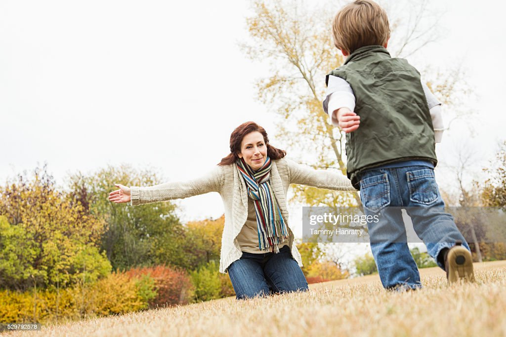 Son (4-5) running to his mother having stretched arms : Bildbanksbilder