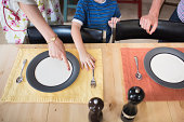 Son setting the table, mother pointing