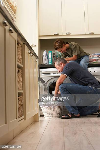 Son (9-11) sitting on counter by father loading washing machine