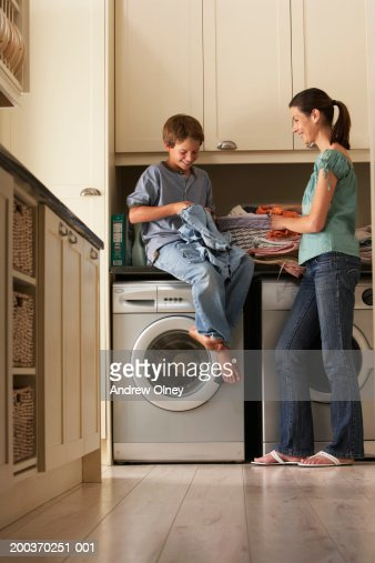 Son (9-11) sitting on counter helping mother with laundry, smiling